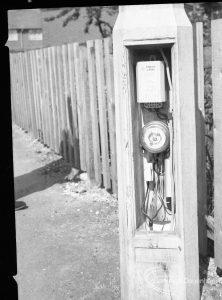 Dagenham street lighting, showing timer working in pillar, next to fence in Crescent Road, 1965