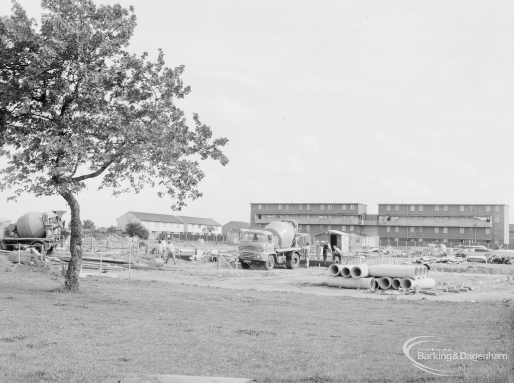 South side of Becontree Heath cleared for new development, with drain pipes and concrete mixers in front of Althorne Way flats under construction, and tree at left, 1966