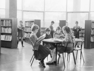 London Borough of Havering Central Library, Romford, showing junior library, with children sitting and reading at table, 1967