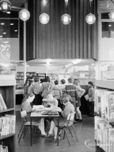 London Borough of Havering Central Library, Romford, showing junior library, with group of readers and light globes on ceiling, 1967