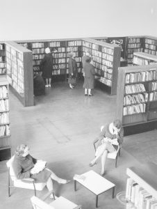 London Borough of Havering Central Library, Romford, showing part of the lending department, with two women resting in armchairs and seen from above, 1967