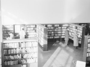 London Borough of Havering Central Library, Romford, showing part of the lending department, with bookcases and library users, 1967
