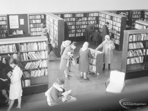 London Borough of Havering Central Library, Romford, showing part of the lending department, with bookcases, library users, and women looking at books on trolley, 1967