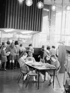 London Borough of Havering Central Library, Romford, showing junior library, with schoolgirls reading at table and groups of children looking at books in background, 1967