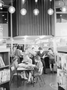 London Borough of Havering Central Library, Romford, showing junior library, with groups of readers, standing and seated, and light globes on ceiling, 1967
