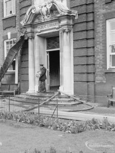 Fire at Barking Central Library, showing fireman at main entrance to building, 1967