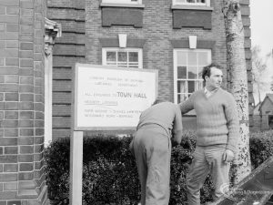 Fire at Barking Central Library, showing noticeboard being displayed in front of building with emergency instructions, 1967