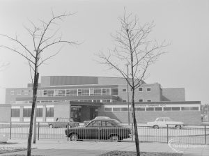 Dagenham Swimming Pool, Becontree Heath from north-east, framed between two bare spindly trees, 1972