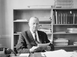 London Borough of Barking Borough Librarian Mr E W McManus FLA at his desk, looking down at a paper, 1972