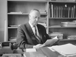 London Borough of Barking Borough Librarian Mr E W McManus FLA, at his desk and reading an open booklet, 1972