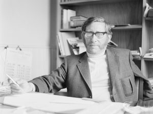 London Borough of Barking Deputy Borough Librarian Mr L Cannon FLA, sitting at his desk with arms extended, 1972