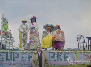 Dagenham Town Show 1972 at Central Park, Dagenham, showing women and girls dressed in long floral dresses and hats and standing on a supermarket float, 1972