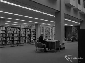 New Barking Central Library, Axe Street, Barking, showing architecture, bookcases, and Mrs Harrison at desk in Lending section, 1974