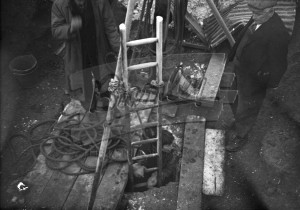 Man emerging from hole by ladder,  1950s