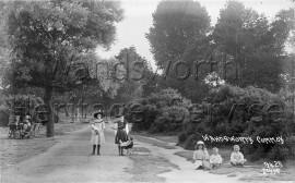 Wandsworth Common – children sitting on grass, woman with pram